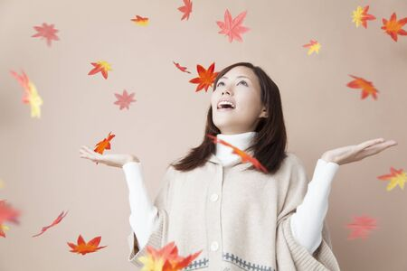 rejoice: women who rejoice in the autumn leaves fall Stock Photo