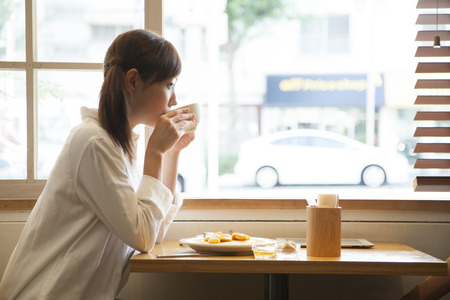 Woman drinking coffee in the Cafe Stock Photo