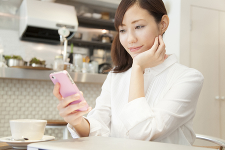 Women who operate the smart phone in a cafe