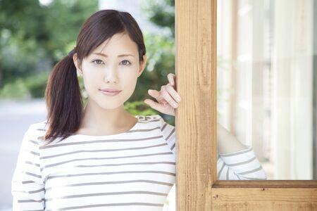 leaned: Women smile leaned on the door Stock Photo