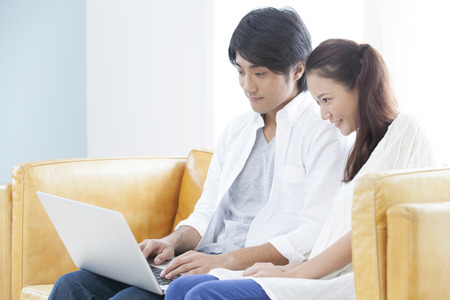 Couple to operate the notebook PC in the living room 版權商用圖片