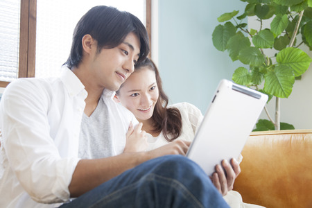 Couple to operate the tablet PC in the living room 版權商用圖片