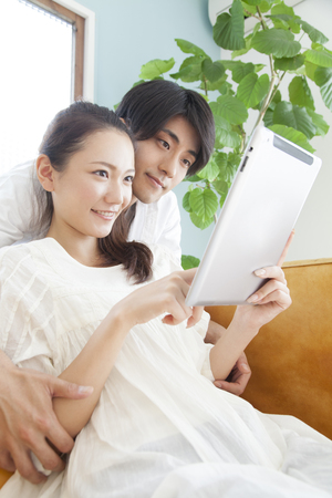 seres vivos: Couple to operate the tablet PC in the living room Foto de archivo