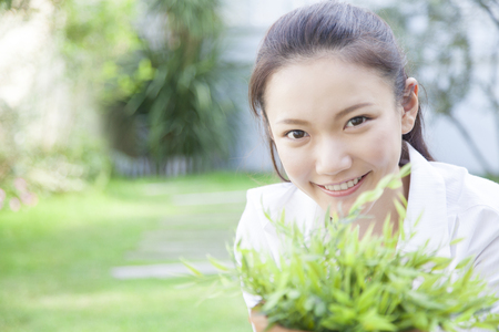 potted plant: Woman smiling with a potted plant Stock Photo