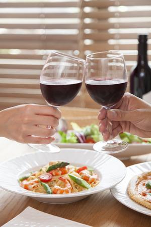 男性と女性の手の赤ワインで乾杯