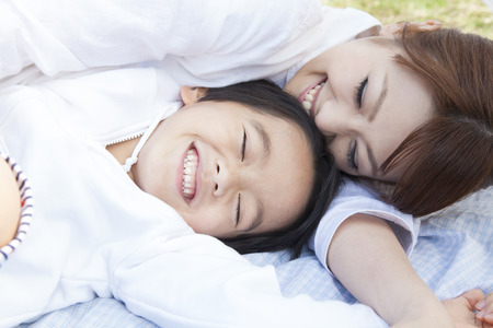 lie down: Mother and child lie down and play Stock Photo