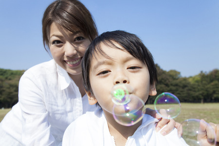 young fellow: Mother and child playing with bubbles