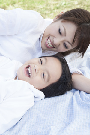 lie: Mother and child lie down and play Stock Photo