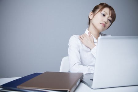 stiffness: office lady suffering from shoulder stiffness
