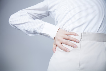 low back pain: From behind the office lady who suffer from low back pain Stock Photo