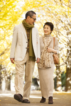 ancianos caminando: Pareja mayor caminando bajo el ginkgo arbolado