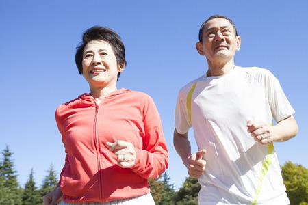 Senior couple jogging through the park