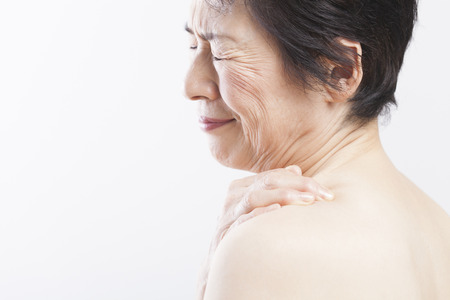 stiffness: Senior woman suffering from shoulder stiffness