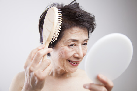 combing hair: Senior woman combing hair Stock Photo