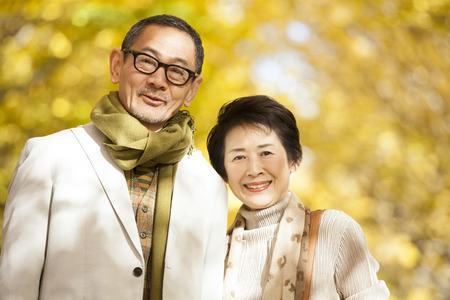 イチョウ並木の下で笑っている年配のカップル 写真素材