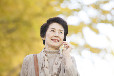 happy asian people: Senior woman to call under the ginkgo