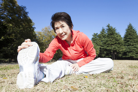 lithe: Senior woman to stretch in the park Stock Photo