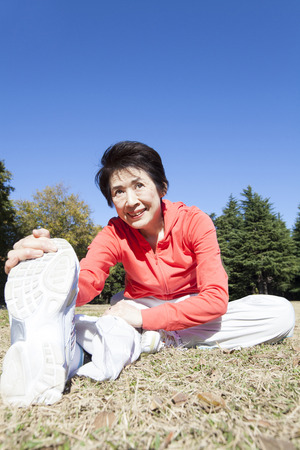 pliable: Senior woman to stretch in the park Stock Photo