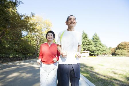 先輩カップルの公園でジョギング 写真素材