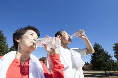 Senior couple drinking water after exercise Stock Photo