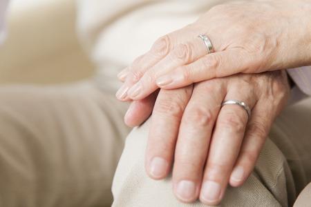 držení: Starší pár překrývajících rukou a rukou