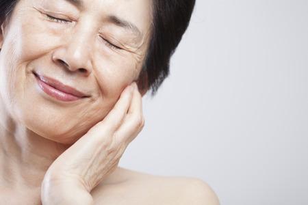 年配の女性が頬に手を置く 写真素材