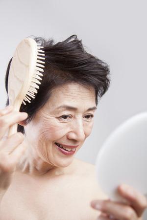 年配の女性は、髪をとかす 写真素材