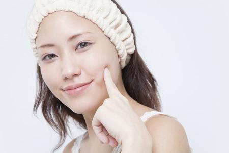 女性は笑みを浮かべて指で頬を保持 写真素材