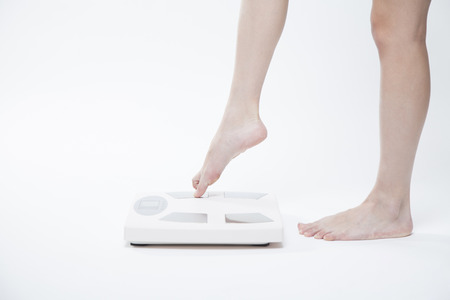 Feet of the women get on the scales