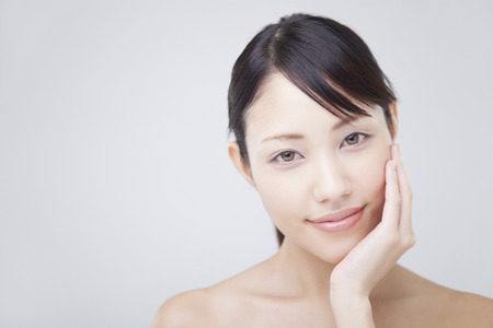 Woman keeps his hand on the cheek and smile