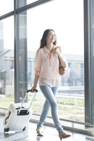スーツケースを引いて歩いている女性