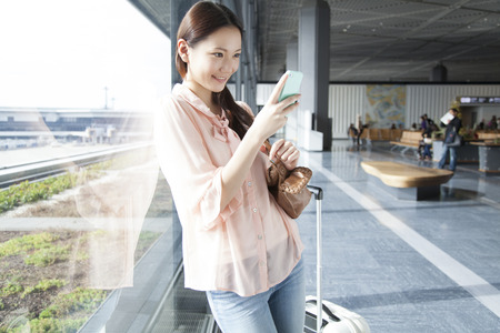 Women working smart phones at the airport