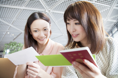 mutually: Women who mutually confirm the airline ticket Stock Photo