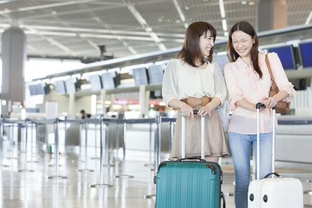 person traveling: Mujeres para el chat en el aeropuerto de salida del vestíbulo