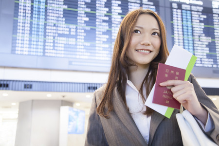 Businesswoman to smile in front of the timetable of the airplane Banque d'images
