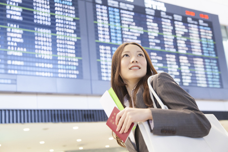 impatience: Businesswoman to look back in front of the timetable of the airplane Stock Photo