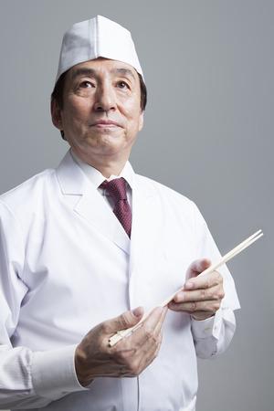 Cook with chopsticks Standard-Bild