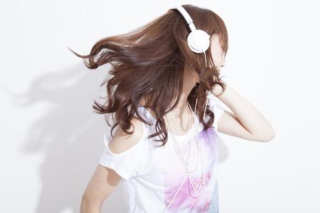 Vrouw die aan muziek met hoofdtelefoons luistert Stockfoto