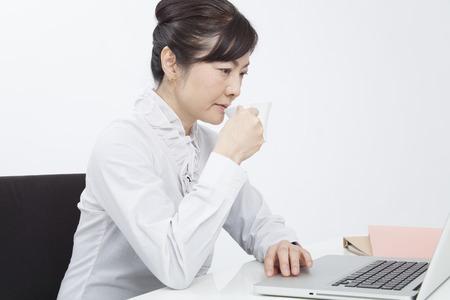 コーヒーを飲みながら PC に向かって実業家