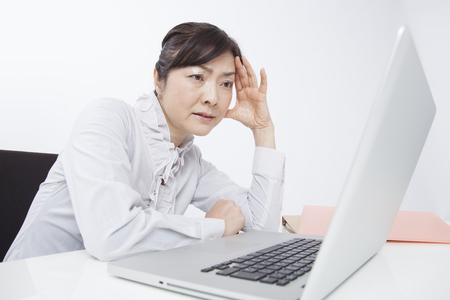 Business woman suffering from in front of the PC photo