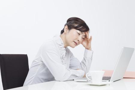 PC の前から苦しんでいる女性実業家
