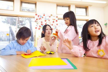 幼稚園児が折り紙を折る
