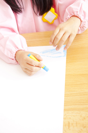 teaching crayons: Kindergarten girls draw pictures with crayons in hand Stock Photo