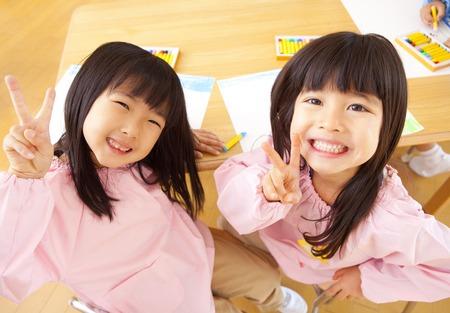 Twee kleuterschool meisjes om het vredesteken