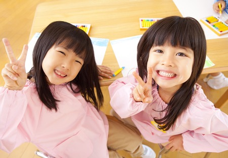 buddies: Two kindergarten girls to the peace sign