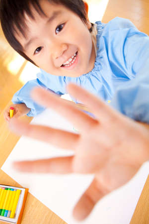 smocking: Kindergarten boys draw with crayons