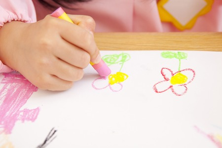smocking: Kindergarten girls draw pictures with crayons in hand Stock Photo