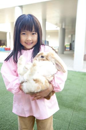 smocking: Kindergarten girls to hug a rabbit