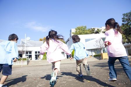 Rear View of kindergarten children running the playground Stock Photo