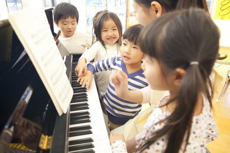mujer hijos: Jardín de infancia se acumule en el piano de los maestros de jardín de infantes Foto de archivo